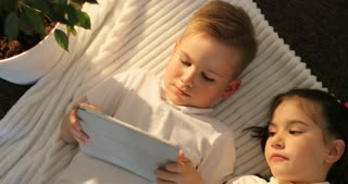 Top view of boy and girl using tablet while lying in floor. Little kids looking at touch pad at home