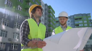 Two caucasian architects in protective helmets and green vest, talking about drawing and construction process. Outdoor.