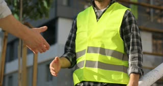Two construction workers in green uniform at the bulding object shaking hands. Outdoor.