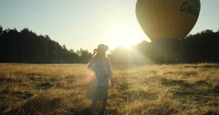 View from behind on the Caucasian young man and woman walking in the field to the big balloon on the picturesque sunset.
