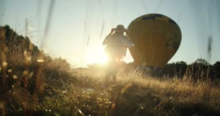 View from below and grass on the happy young couple running in the field to the big balloon on the picturesque sunset.