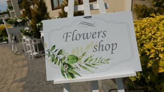 White flowers for wedding ceremony on restaurant background with signboard from the flowers shop. Close up shot.