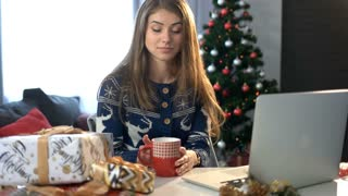 Woman drinking coffee at the table with christmas decoration and laptop on the christmas tree background in the living room.