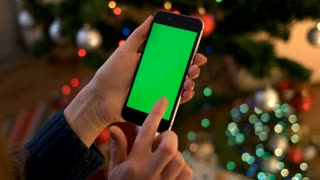 Woman hands typing on vertical smartphone with green screen on background with bokeh from garland. Close up. Chroma key.