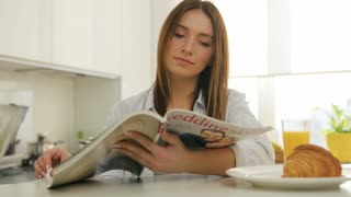 Woman thumbing through the magazine in the kitchen during breakfast