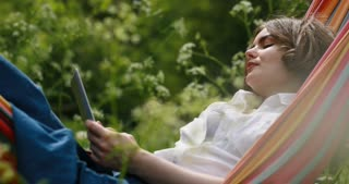 Woman using mobile phone in a hammock on green forest. Young woman lying down on a hammock in summer using a digital tablet.