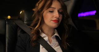 Woman works at a laptop in the backseat of car city lights background