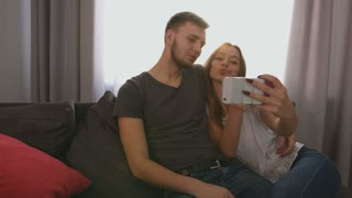 Young attractive couple in love making a selfie in living room at home, making funny faces and smiling on camera. Side view.
