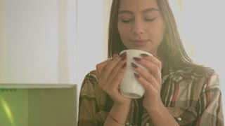 Young attractive woman drinking tea and smiling at camera in the kitchen. Close up.