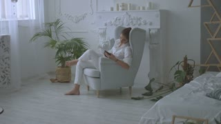 Young attractive woman in white casual clothes using tablet while sitting in chair in the living room.