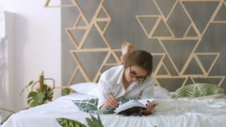 Young beatiful woman in casual shirt reading book while lying on the bed.
