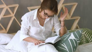 Young beatiful woman relaxing at home while reading on the bed.