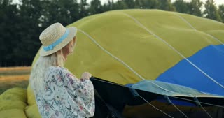 Young blonde good looking woman standing in the field and trying to fix a balloon before fly in it. Summer day.