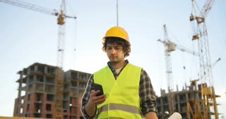 Young builder with black curly hair in yellow helmet talking on mobile phone with friend, smiling on unfinished construction background.