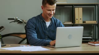 Young business man in casual shirt working in the laptop in the stylish office, finishing work day and feeling so happy.
