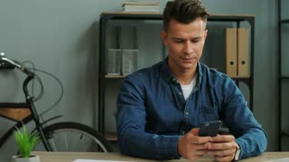 Young business man using smart phone for talking with partner in the office background.