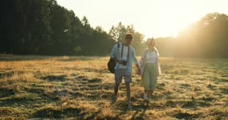 Young Caucasian happy girlfriend and boyfriend walking hand in hand with a camera in the field on the summer sunset.