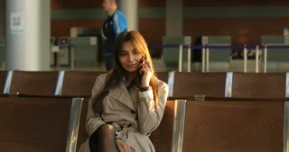 Young elegant business woman with hand luggage in international airport, Talking on cell phone.