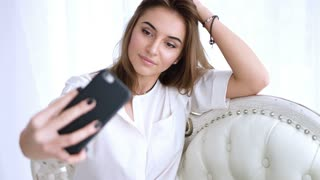 Young girl taking a selfie sitting on the sofa Young brunette girl takes photograph of herself on mobile phone, a selfie