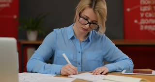 Young girl working with documents in modern office. Skilled professional female administrative manager checking documentation.