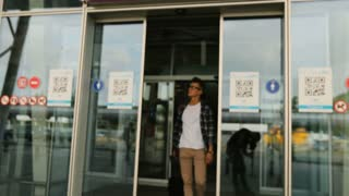 Young handsome man in the glasses with the baggage walking from the door of modern airport terminal to his home. Dolly shot.