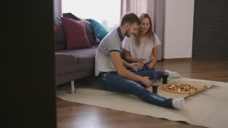 Young happy man and woman sitting on the floor at home and eating tasty pizza. View from the side.