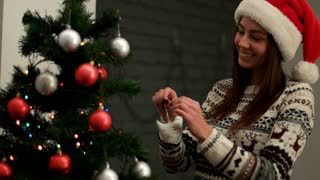 Young happy woman in santa claus hat smiling and decorating a Christmas tree red and silver toys. Close up.