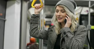 Young happy woman talking on the phone and holding handrail publick transport.