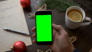 Young man hand typing on smart phone with green screen on background with christmas tea with fir, red toys, stars and garland on brown wood table. Christmas decoration. Top view. Chroma key.