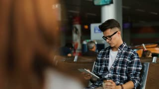 Young man in casual shirt talking on smart phone with friends and drinking the coffee while sitting in the airport lounge.