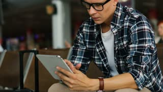 Young man in casual shirt using tablet for chatting with someone and removing the glasses while sitting in the airport lounge.