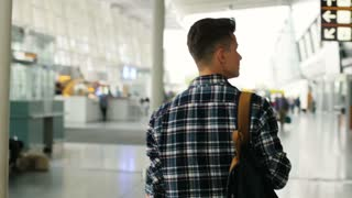 Young man in casual shirt with the baggage walking in the modern airport terminal. Dolly shot. View from the back.