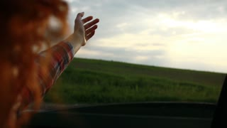 Young red hair woman feeling wind through car window on nature background.