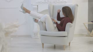Young sexy woman using smart phone for chatting while relaxing in the chair on the white background.