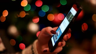 Young woman hands fliping through the instagram on black smart phone at christmas eve at home. Close up.