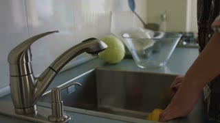 Young woman hands washing red pepper under tap water in the kitchen. Close up.