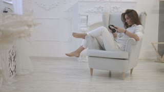 Young woman in casual shirt listening music in headphones, using smart phone while sitting in the chair in home.