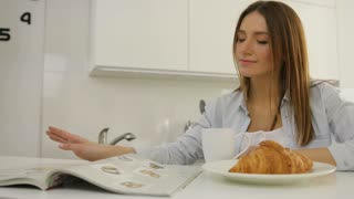 Young woman thumbing through the magazine in the kitchen during breakfast