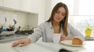 Young woman thumbing through the magazine in the kitchen.