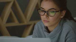 Young woman with glasses looking at the monitor, surfing the Internet