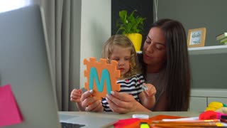 Young woman with long black hair and her little dauther with blond curly hair considering the figure of plasticine siting on the desk at home. Indoor.