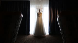 wedding dress hanging in front of the window
