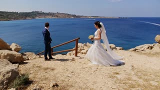 young bride and groom walking on the beach, kissing and having fun
