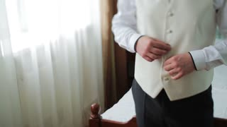 Young bride dress and shirt buttons. Happy young groom on their wedding day. Man buttoning his shirt in front of a window. Wedding concept.