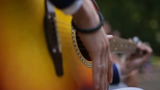 Young Musician Playing Solo On Classic Guitar, Finger style Close Up. An acoustic guitar uses only acoustic means to transmit the strings' vibration energy to the air in order to make a sound
