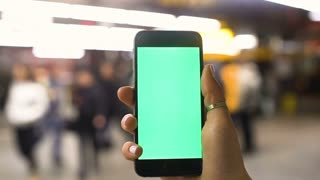 4K Close up of hand holding a smartphone with green screen display at underground train station. Shot on RED Epic.