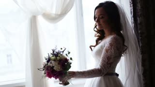A bride of incredible beauty holding bridal bouquet at her left hand and smelling flowers aroma.