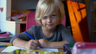 A child with long blond hair is painting something with markers pens, looking away