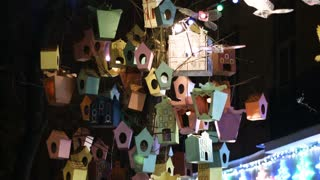 A collection of decorative bird houses, wooden feeders on the tree in city