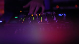 A DJ touching buttons to control the sound closeup